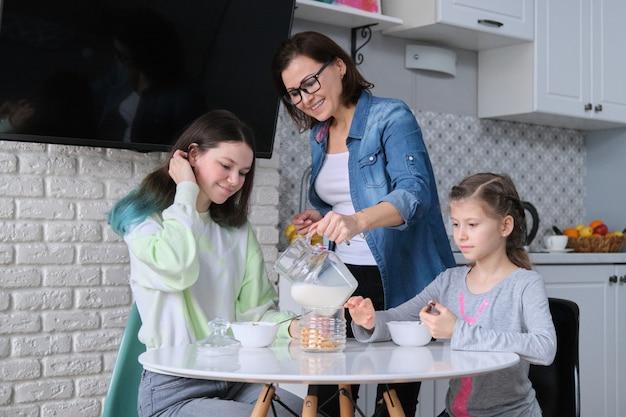 Glückliche mutter, die töchter in der küche kümmert