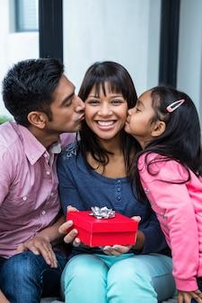 Glückliche mutter, die von ihren kindern beim halten eines geschenkes geküsst wird