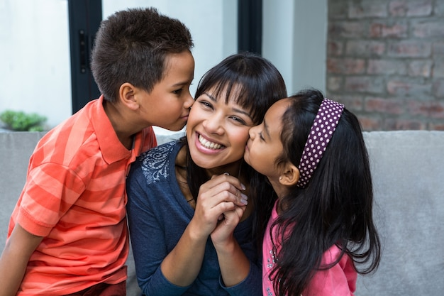 Glückliche mutter, die von ihren kindern geküsst wird