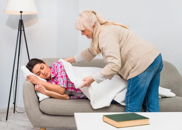 Glückliche mutter, die weiße decke über ihrer tochter zu hause schläft auf sofa setzt