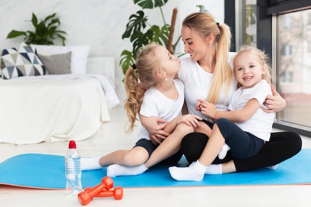 Glückliche mutter, die zu hause auf yogamatte mit töchtern aufwirft