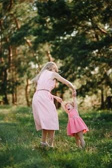 Glückliche mutter dreht die tochter im sommerurlaub in der natur. mutter und mädchen, die bei sonnenuntergang im park spielen. konzept der freundlichen familie. nahaufnahme.
