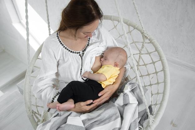 Glückliche mutter füttert das baby in einer weißen hängematte. glückliches mutterschaftskonzept.