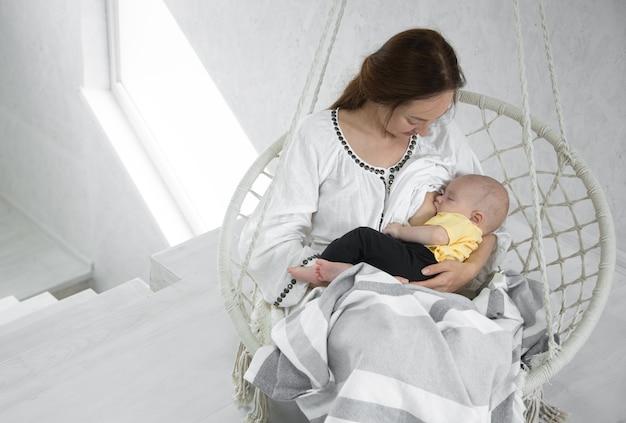 Glückliche mutter füttert ein baby in einer weißen hängematte mit einer decke eines weißen raumes. glückliches mutterschaftskonzept.