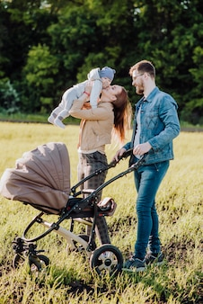 Glückliche mutter hält das baby in ihren armen und küsst es