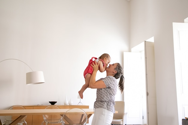 Glückliche mutter hält kleines mädchen, erhebt sie und lacht. lustiges baby, das spaß mit liebender mutter drinnen hat und gesicht mit handflächen schließt. familienzeit, mutterschaft und zuhause sein konzept