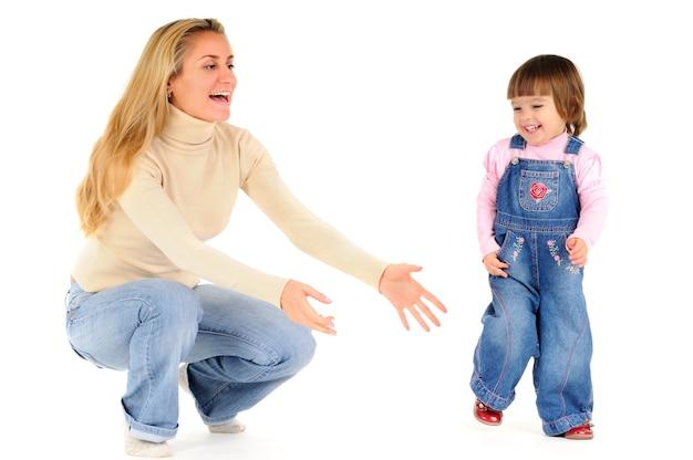 Glückliche mutter hält und spielt mit ihrer kleinen tochter in rosa kleidung über weißer wand. schönes glückliches kinderlebensstilkonzept