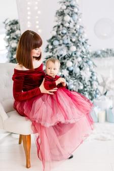 Glückliche mutter im kleid, sitzt mit ihrer kleinen tochter auf den knien und genießt die weihnachtszeit