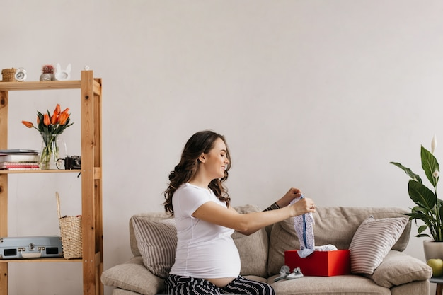 Glückliche mutter im weißen t-stück und in der hose schaut auf ihre zukünftigen babykleidung