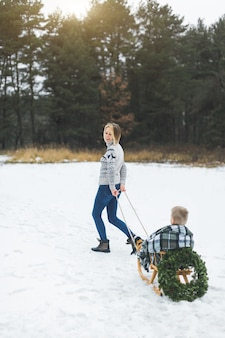 Glückliche mutter in strickpullover und jeans trägt ihren kleinen sohn auf einem holzschlitten
