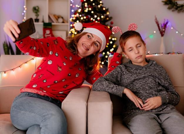 Glückliche mutter in weihnachtsmütze macht selfie mit smartphone mit ihrem kleinen sohn, der auf einer couch in einem dekorierten zimmer mit weihnachtsbaum in der wand sitzt