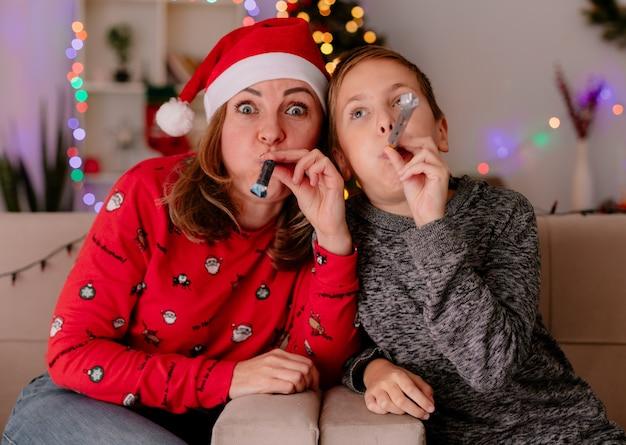 Glückliche mutter in weihnachtsmütze mit ihrem kleinen sohn, der auf einer couch sitzt und spaß beim pfeifen in einem dekorierten raum mit weihnachtsbaum in der wand hat