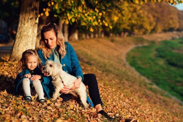 Glückliche mutter mit ihrem kind, das mit hund des weißen terriers auf herbstblättern sich entspannt