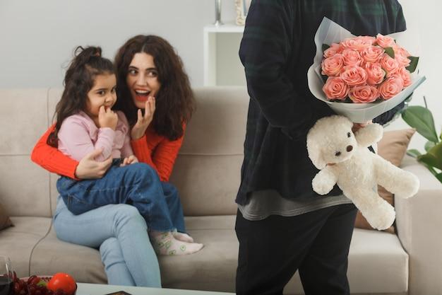 Glückliche mutter mit ihrem kleinen kind tochter sitzt auf einer couch und sieht erstaunt und überrascht aus, während sie einen blumenstrauß vom ehemann erhält, der den internationalen frauentag feiert