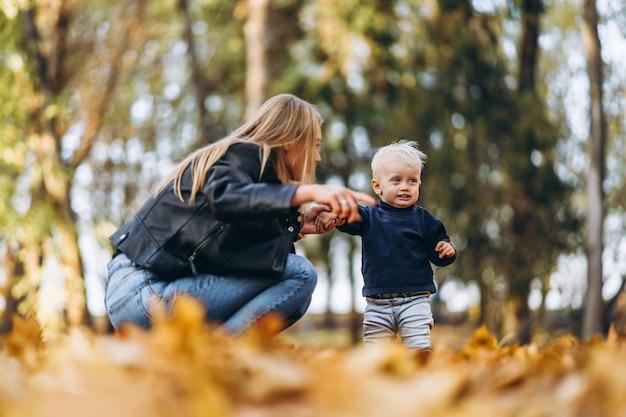 Glückliche mutter mit ihrem kleinen kleinen sohn, der spaß im park hat