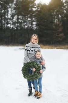 Glückliche mutter mit ihrem kleinen sohn, der auf dem hintergrund des winterwaldes draußen steht