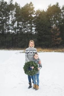 Glückliche mutter mit ihrem kleinen sohn, der draußen steht und weihnachtskiefernkranz hält.