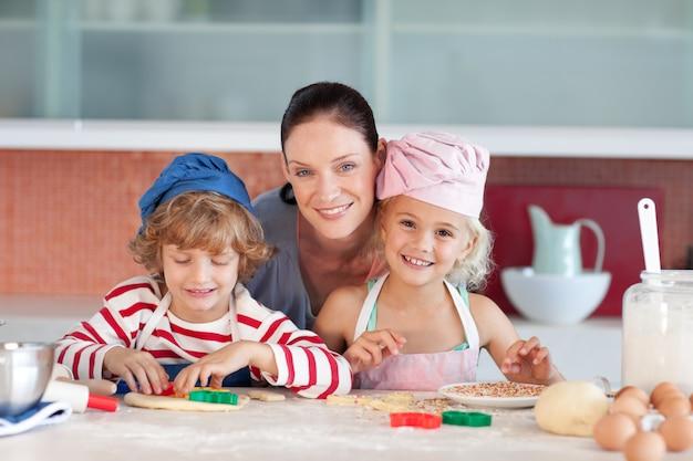 Glückliche mutter mit ihren kindern backen