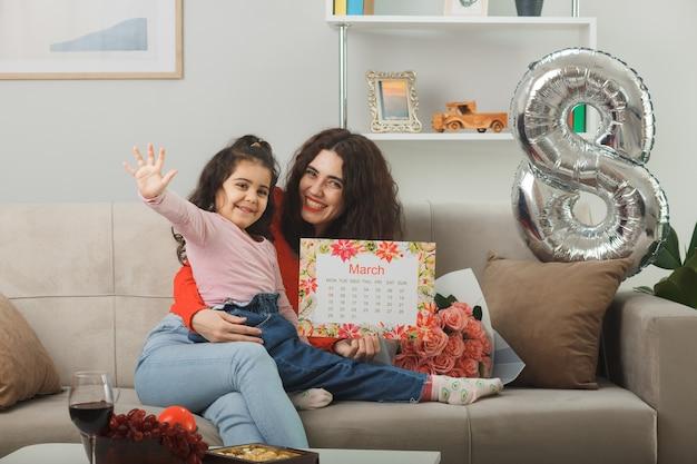 Glückliche mutter mit ihrer kleinen tochter, die auf einer couch mit blumenstrauß und kalender des monats märz sitzt und fröhlich im hellen wohnzimmer lächelt, um den internationalen frauentag am 8. märz zu feiern