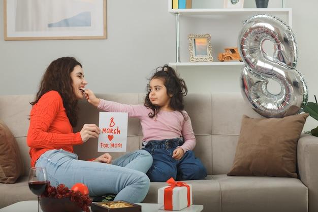 Glückliche mutter mit ihrer kleinen tochter, die auf einer couch sitzt und eine grußkarte hält, die fröhlich im hellen wohnzimmer lächelt und den internationalen frauentag am 8. märz feiert