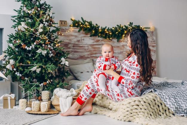 Glückliche mutter mit ihrer kleinen tochter in der feiertagskleidung mit den druckrotwild und schneeflocken, die spaß auf dem bett im gemütlichen raum mit einem weihnachtsbaum und weihnachtslichtern haben. neujahr und weihnachten konzept.