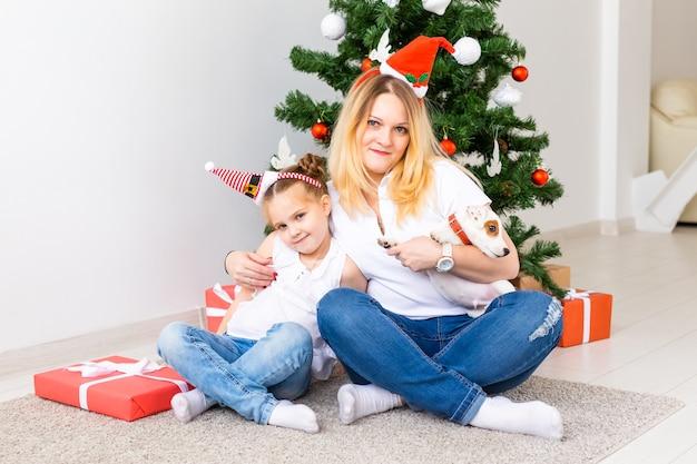 Glückliche mutter mit ihrer tochter und dem jack-russell-terrier-hund, der in der nähe des weihnachtsbaums sitzt