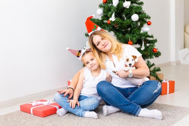 Glückliche mutter mit ihrer tochter und jack russell terrier hund sitzen in der nähe des weihnachtsbaumes