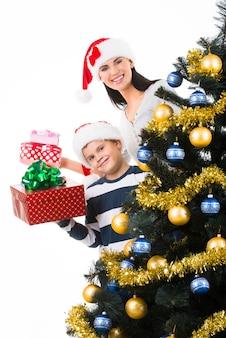 Glückliche mutter mit kind halten schachtel mit geschenk nahe dem weihnachtsbaum