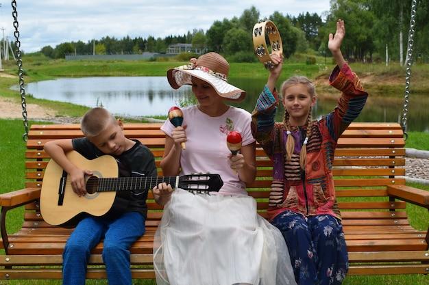 Glückliche mutter mit kindern, die musik spielen