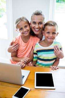 Glückliche mutter mit kindern durch technologie zu hause