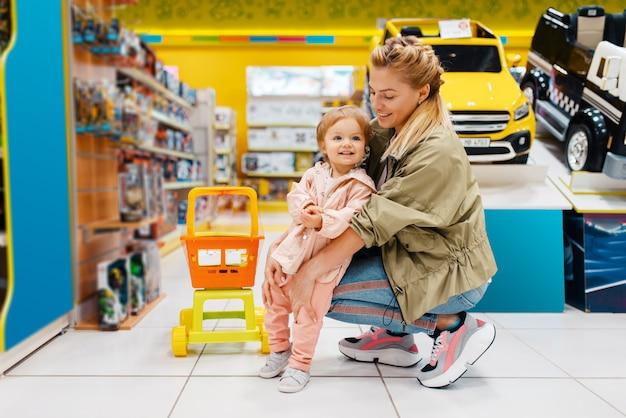 Glückliche mutter mit kleiner tochter im kindergeschäft. mutter und kind wählen zusammen spielzeug im supermarkt