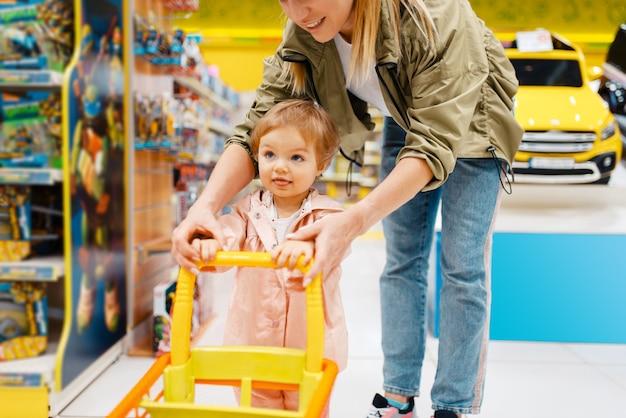 Glückliche mutter mit kleiner tochter im kindergeschäft