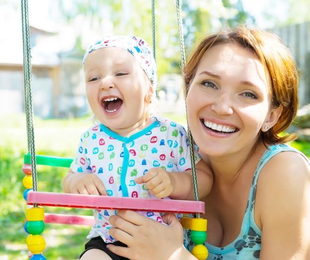 Glückliche mutter mit lachendem baby sitzt auf der schaukel