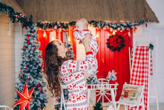 Glückliche mutter mit seiner kleinen tochter in der feiertagskleidung mit druckrotwild und schneeflocken in verziertem raum mit einem weihnachtsbaum und einem kranz