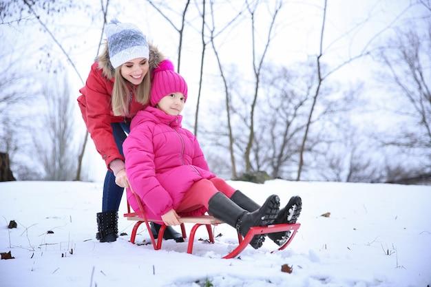 Glückliche mutter mit tochter, die im winterurlaub im verschneiten park rodelt