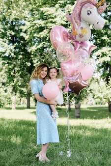 Glückliche mutter mit zweijährigem mädchen mit ballons, die geburtstagsfeier feiern