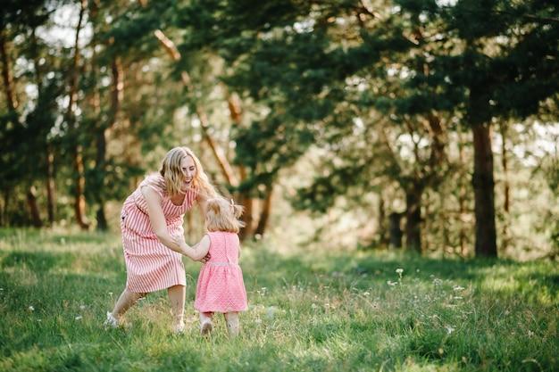 Glückliche mutter rennt und fängt die tochter im sommerurlaub in der natur. mutter und mädchen, die bei sonnenuntergang im park spielen. konzept der freundlichen familie. nahaufnahme.