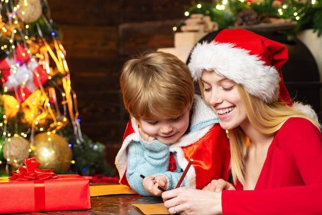 Glückliche mutter schreibt mit ihrem schönen sohn einen brief an den weihnachtsmann. frohe weihnachten familie. neujahrszeit