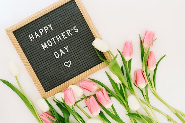 Glückliche mutter-tagesaufschrift an bord mit hellen tulpen