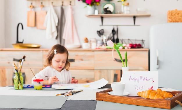 Glückliche mutter-tagesaufschrift auf tabelle nahe malendem mädchen