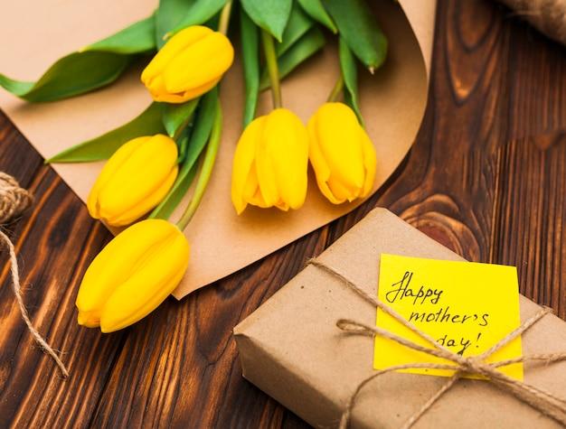 Glückliche mutter-tagesaufschrift mit gelben tulpen und geschenk