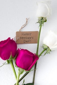 Glückliche mutter-tagesaufschrift mit rosen auf leuchtpult