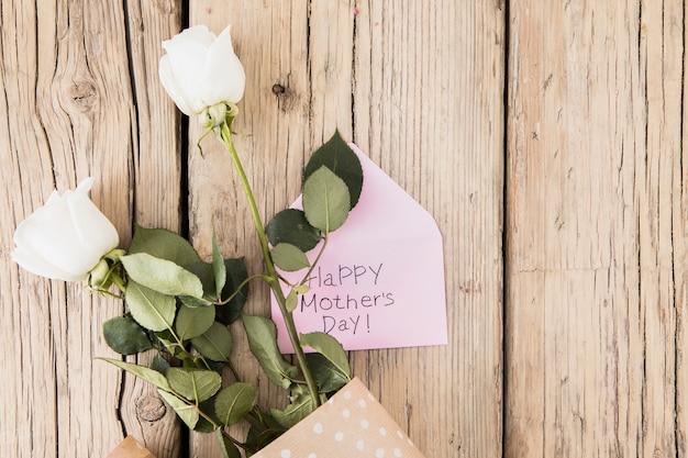 Glückliche mutter-tagesaufschrift mit rosen auf tabelle