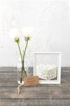 Glückliche mutter-tagesaufschrift mit rosen im vase und im rahmen