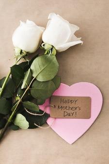 Glückliche mutter-tagesaufschrift mit rosen und papierherzen