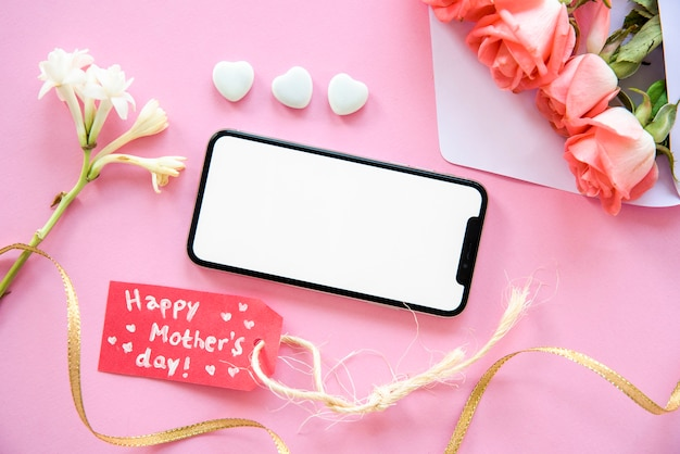Glückliche mutter-tagesaufschrift mit smartphone und blumen