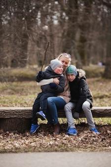 Glückliche mutter umarmt ihre kinder im park