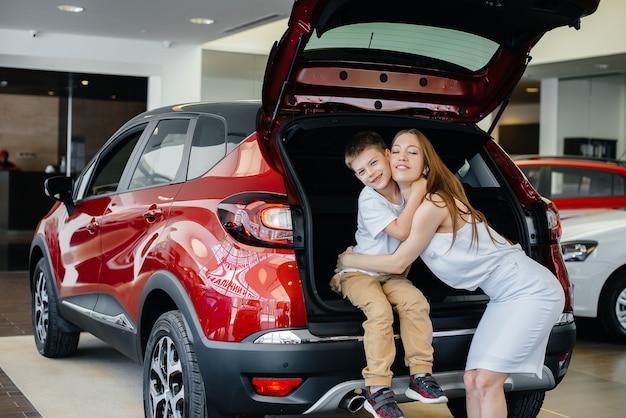 Glückliche mutter umarmt ihren sohn, nachdem sie in einem autohaus ein neues auto gekauft hat.
