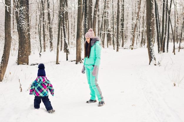 Glückliche mutter und baby im winterpark. familie im freien. fröhliche mama mit ihrem kind.