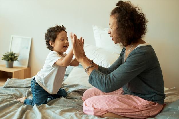Glückliche mutter und baby spielen zu hause. fröhliche lateinische frau, die hände mit ihrem kleinen sohn fasst, der auf bett sitzt